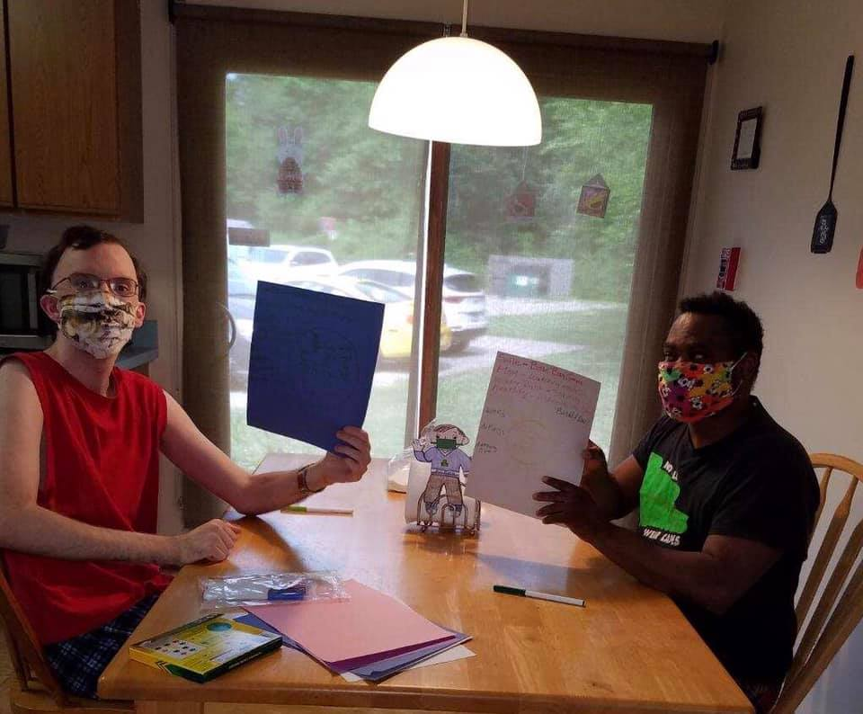 Picture of two men holding up pieces of paper, sitting at a kitchen table