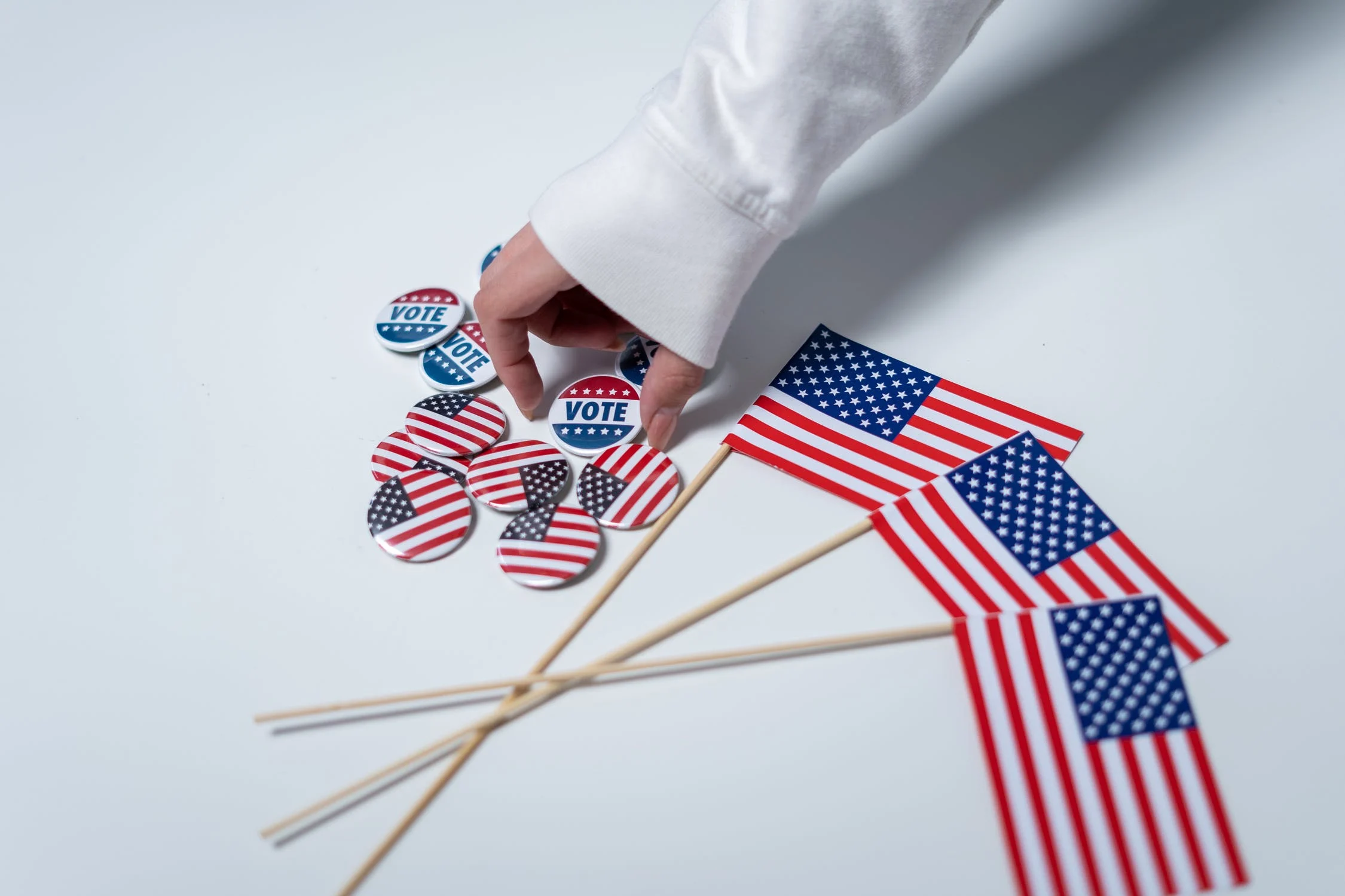 Hand picking up vote button next to small American flags on table