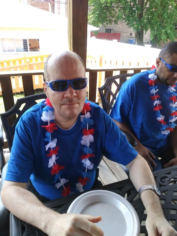 Screen Shot from 7-10-2020 Friday update video man in a blue shirt with a red, white and blue lei