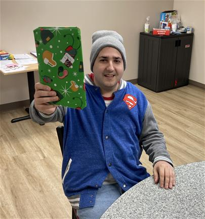 Man holds up a wrapped Christmas present