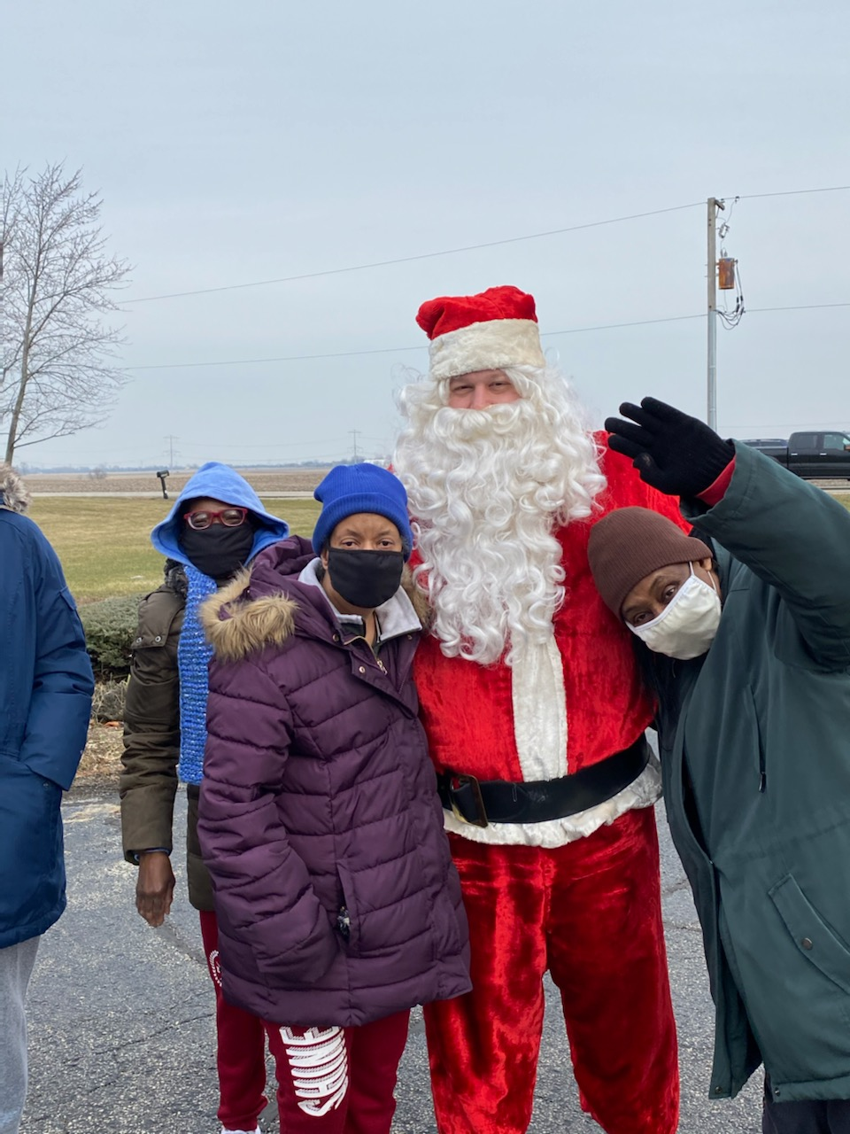 Three women stand beside a man dressed as Santa